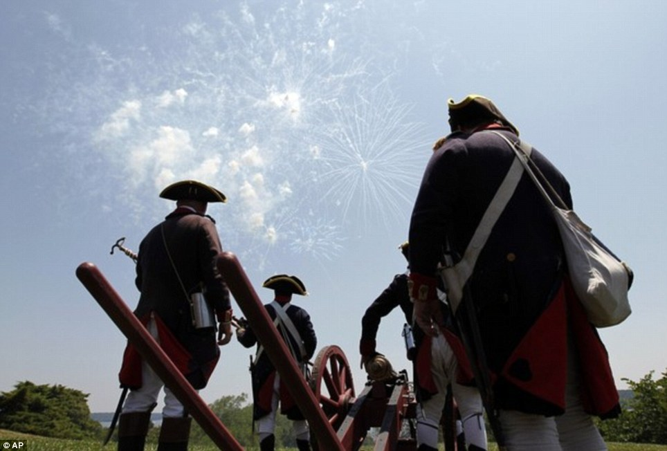 Americans we: Re-enactors in colonial costumes stand by their three-pound canon as they watch daytime fireworks during the event in Alexandria, Virginia
