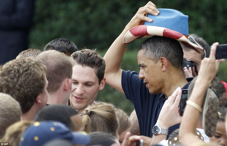 Yee-haw: Mr Obama puts on a red, white, and blue hat, while visiting with service members