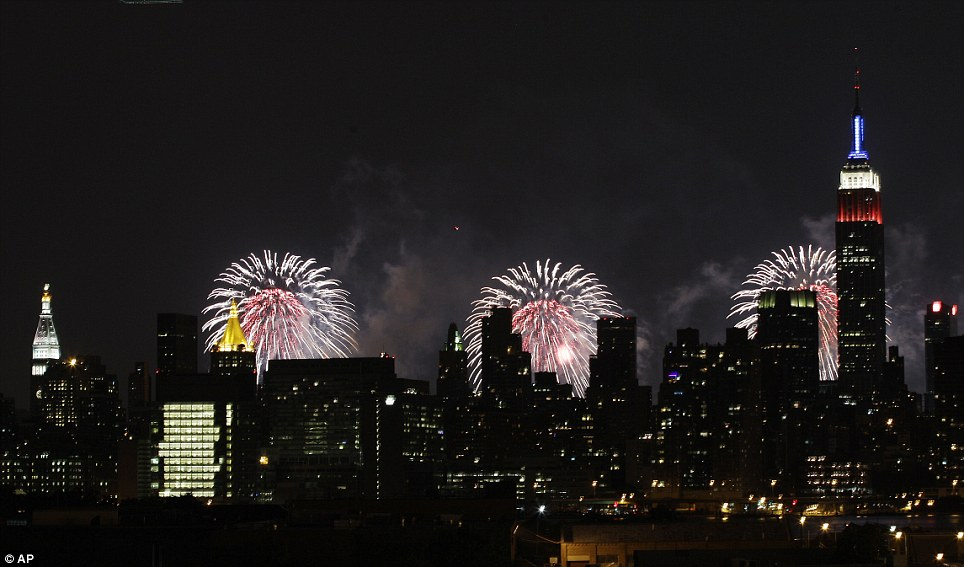 New York symbol: The Empire State Building, illuminated with red, white and blue lights, is seen from the Queens, back-lit by fireworks over the Hudson River during the Macy's Fourth of July fireworks show