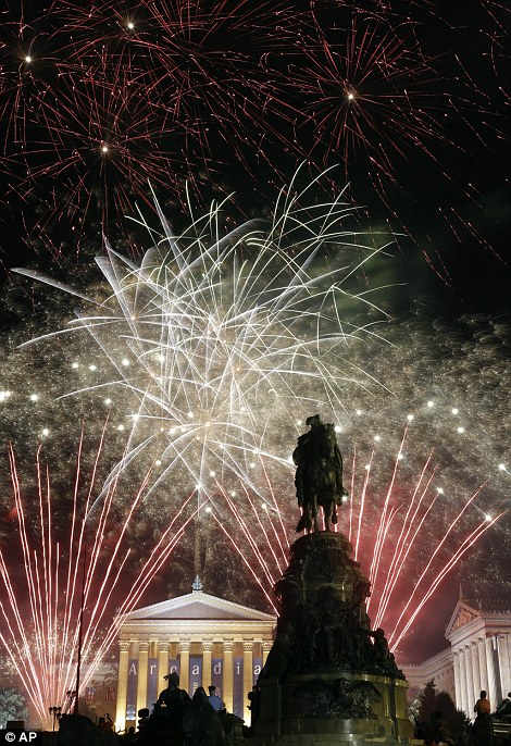 Fireworks explode over the Philadelphia Museum of Art and a statue of George Washington
