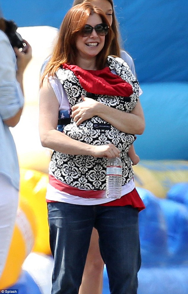 A very Happy Fourth of July! Alyson was seen carrying her precious bundle of joy for the first time at Brentwood's Independence Day celebration this week