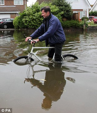 Downpours: A man makes his way on a bike along a flooded road in Felpham, West Sussex, last month as the UK was hit by the wettest June on record