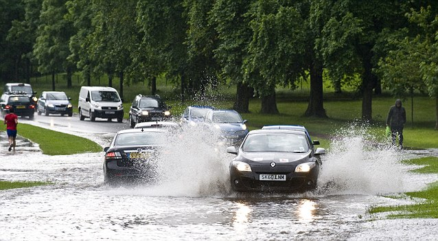 Splash time: Flooding on Queen's Drive, Edinburgh today. Severe flooding is predicted over England throughout the course of Friday and into Saturday