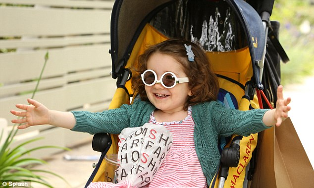 Just like mummy! The youngster put on a pair of cool white sunglasses while being pushed around