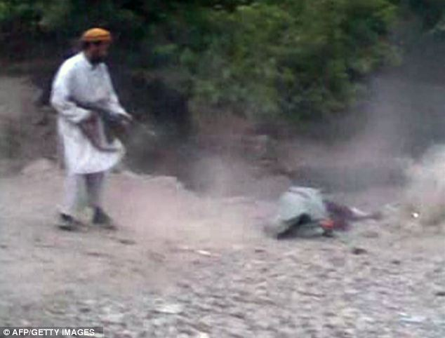The man continues to fire the AK47 rifle at Najiba's dead body as she lies at the place of execution on the outskirts of a village in the, Parwan province, north of Kabul