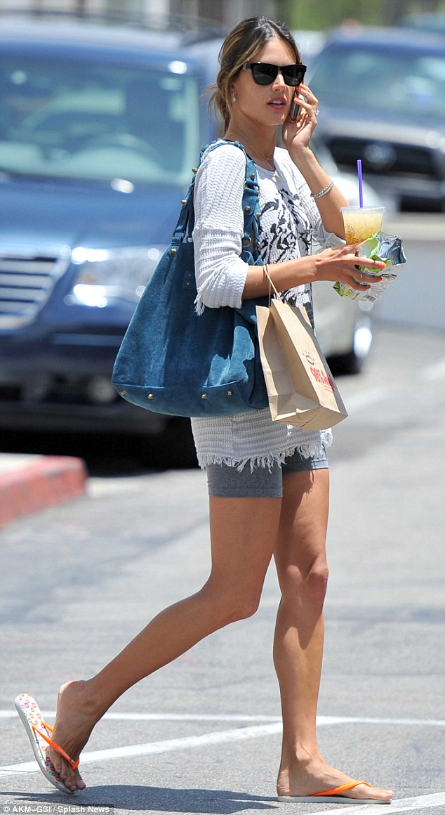 Casual chic: Alessandra later stepped out in grey cycling shorts and orange flip flops
