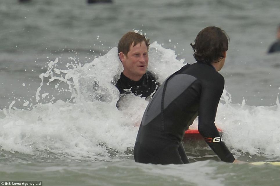 Prince smiles as a wave crashes over him while he body boards towards a friend