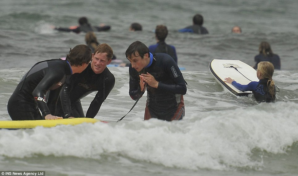 Beach boys: Harry talks to his friends in the surf...