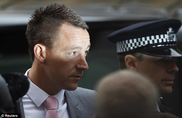 Police protection: Terry wore a pink tie and grey suit for the first day of his trial