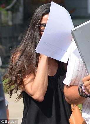 Peek-a-boo! The actress was covering her face with what looked like a film script