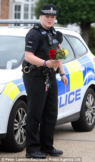 A police woman holding a floral tribute near the scene of Pc Dibell's death