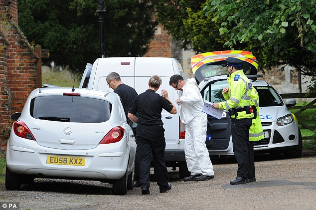 Gathering evidence: Forensics officers and detectives assemble at the gates of All Saints Church as they try to piece together the final moments of Mr Reeve's life