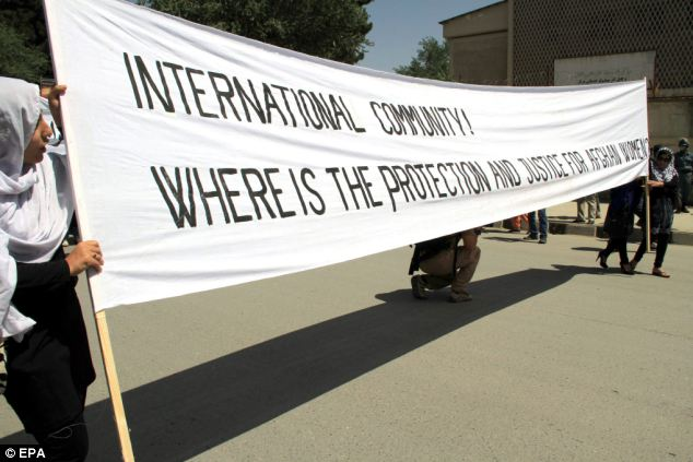 English banners: Choosing an international language to voice their protest, the banner reads, 'International community! Where is the protection and justice for Afghan women?'