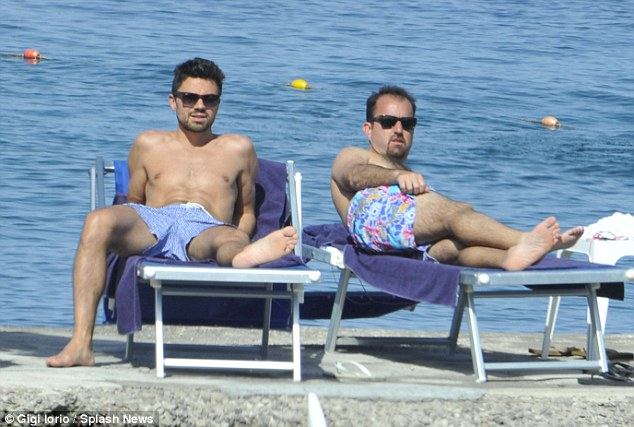 Relaxing: Dominic was also enjoying the rays with a friend on his sun lounger