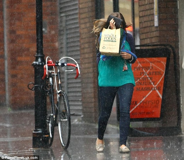 Running for cover: Kim tries vainly to keep the rain off her face using her purse and paper carrier bag