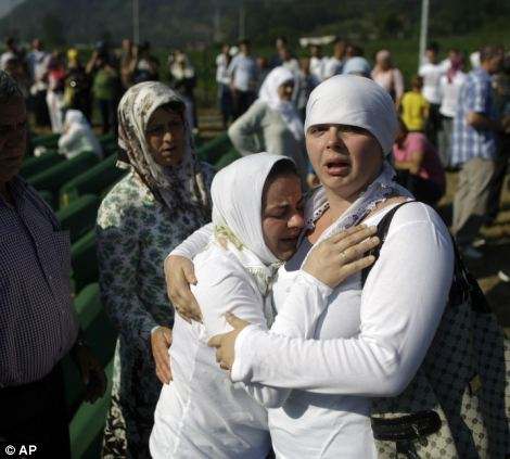 Two women console each other during the mass burial