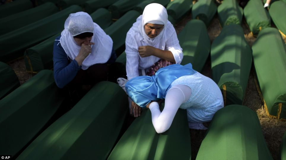 Time to mourn: Three women grieve beside the coffin of their relative at the Potocari memorial complex near Srebrenica