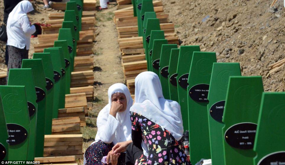 Two Bosnian muslim women sit among 520 body caskets