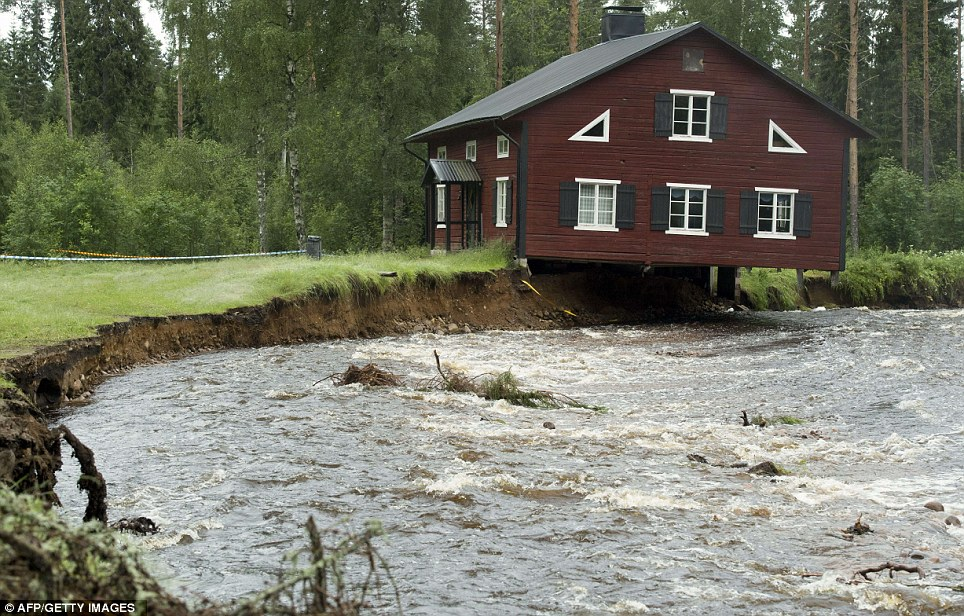 Hanging in the balance: A house sits precariously over a rain-swollen creek in Nyhammar in the county of Dalarna in central Sweden. Its foundations have been washed away