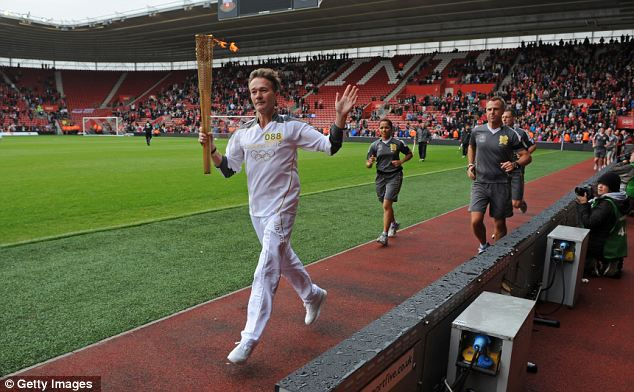 Golden moment: A runner carries the Olympic Flame at St Mary's Stadium