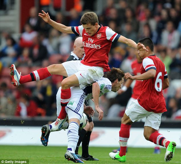 Up for it: Arsenal's Thomas Elsfield tangles with Lucas Biglia of Anderlecht