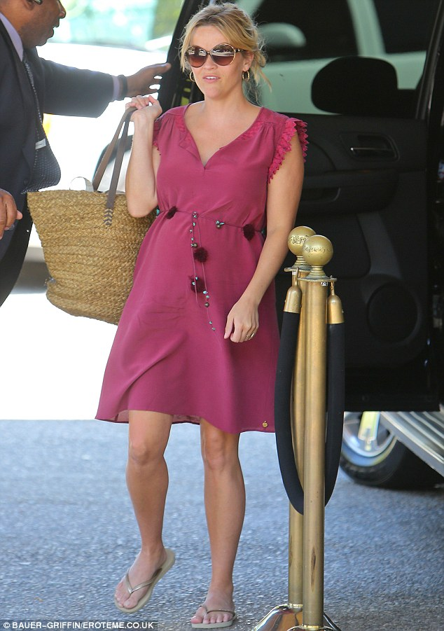 Looking good: She donned a pink frock with embellished belt that emphasised her baby bump