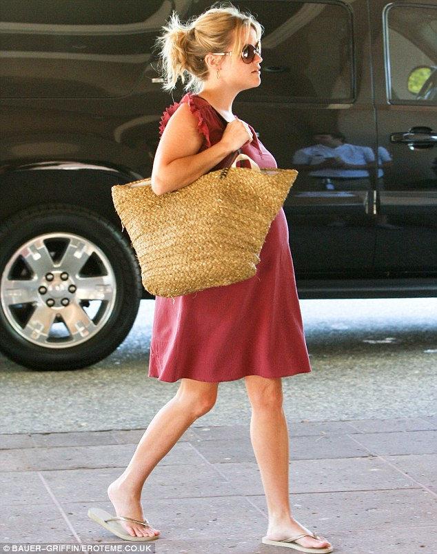 Large load: Reese kept her blonde locks back in a scruffy bun and donned comfortable flip flops