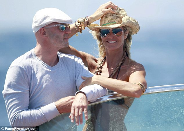 Hat's nice: Elle looked effortlessly stylish in the black bikini, jewellery and her straw hat