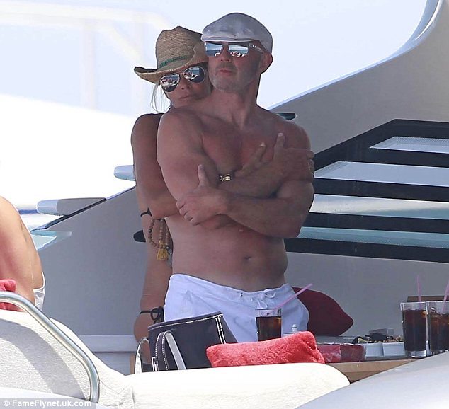 Hands on: Elle was seen wrapping her arms around her man, who despite being 56-year-old still has a gym-honed physique