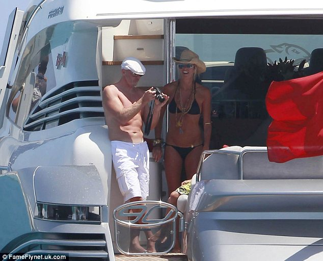 Snap happy: Elle and Roger both had their impressive bodies on display as they stood at the back of their yacht taking a few pictures