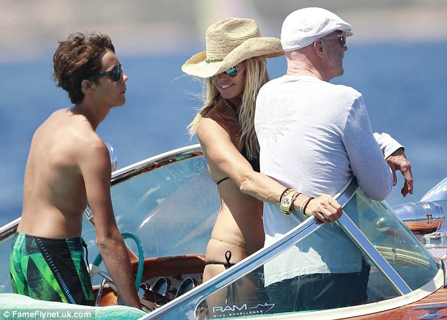 Three's no a crowd: Elle's son Arpad didn't appear to be uncomfortable as he steered the boat next to his mother and her man
