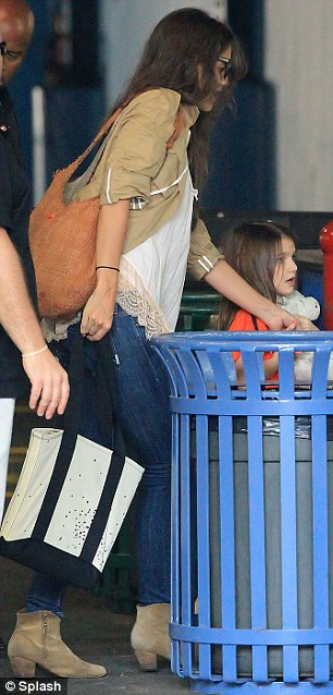 Mother and daughter: Katie wore a smile as she walked Suri through the garage at Chelsea Piers
