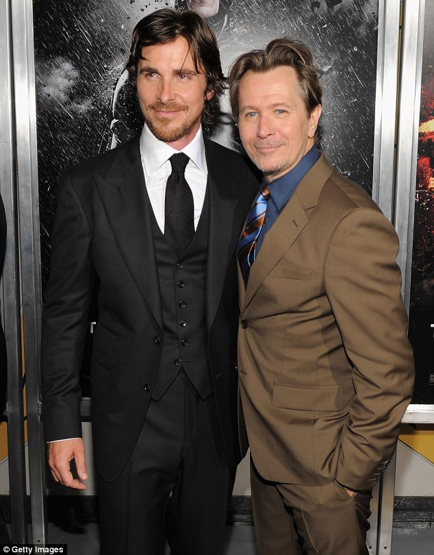 Suited and booted: Christian posed up with co-star Gary Oldman, who wore a brown suit offset with a blue shirt