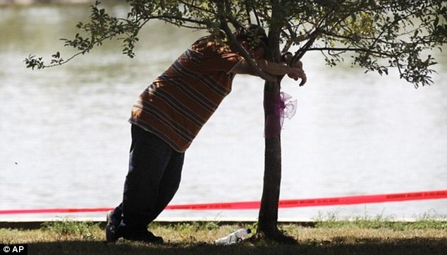 A father's agony: Dan Morrissey leans on a tree near Meyers Lake where his daughter Lyric and her cousin Elizabeth Collins disappeared