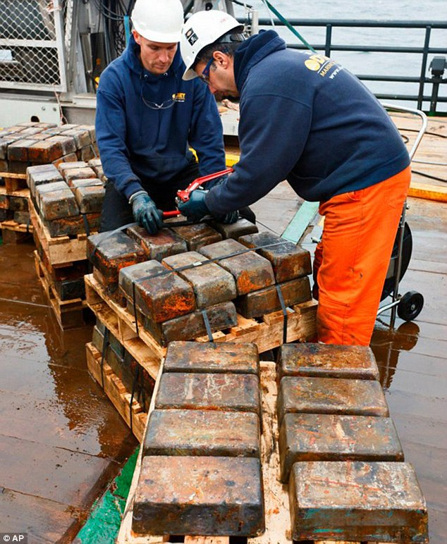 Booty: Salvage workers inspect silver bars as they are recovered from the wreck of the SS Gairsoppa torpedoed in a German U-boat attack 300 miles off the south-west coast of Ireland