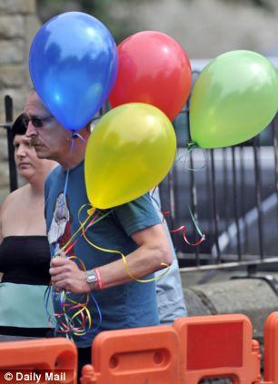 Mourner holds holds balloons
