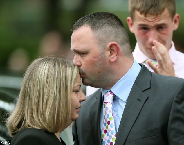 Grief-stricken: Kenny Heaton kisses his wife Michelle - Jamie's mum - as grieving friends and relatives look on