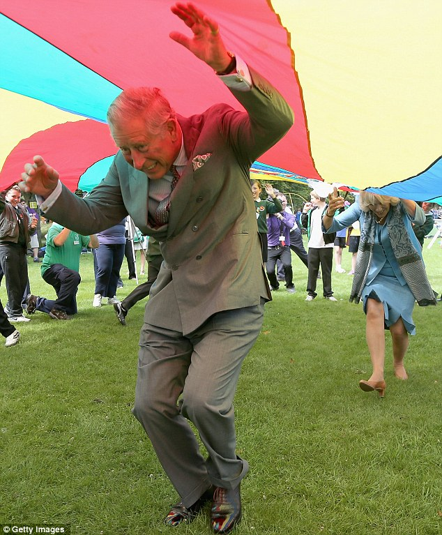 Floating: Charles raises his arms as he attempts to lift the rainbow-coloured silk