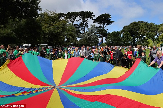 Multi-coloured: The enthusiastic couple admire the metres of parachute before the game starts in Guernsey