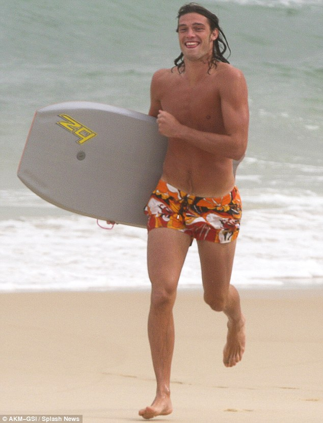 Fun in the sun: Andy Carroll seemed to be having a whale of a time as he sprinted down the beach in Rio de Janeiro, Brazil