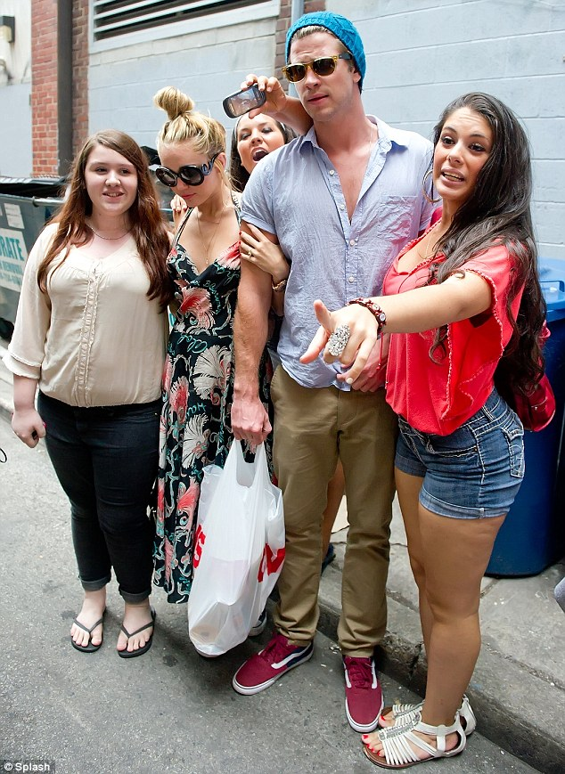 Keeping cool: Miley clung to Liam as the pair dutifully took pictures with fans