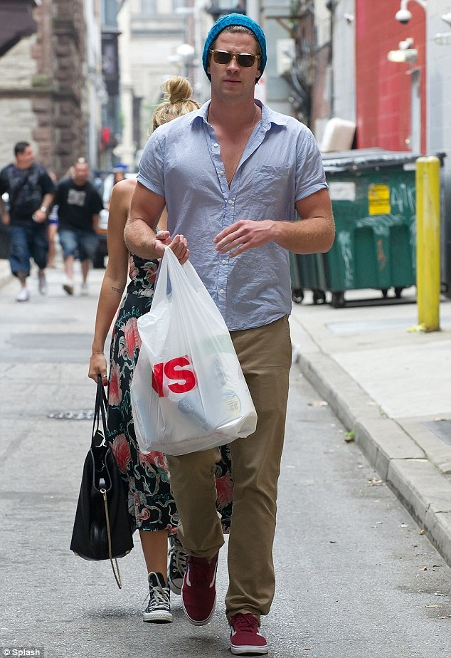 Feeling shy? Miley hid behind Liam as he paved the way with a CVS pharmacy bag