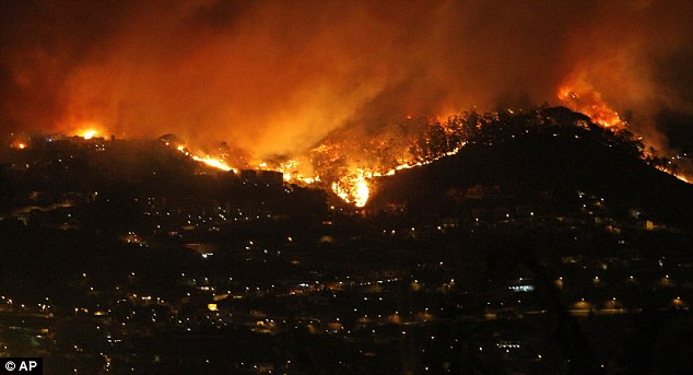 Angry front: A clear line of flames rage on the hills above Funchal, under choking smoke