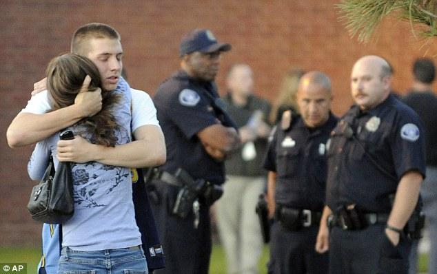 Grief: Witness Jacob Stevens, 18, hugs his mother Tammi after being interviewed by police on Friday