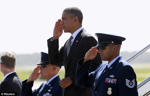 'Heartbroken': Obama salutes as he steps from Air Force One in Fort Myers, Florida. He has said he will cut short his campaign swing through the state in light of the tragedy in Colorado