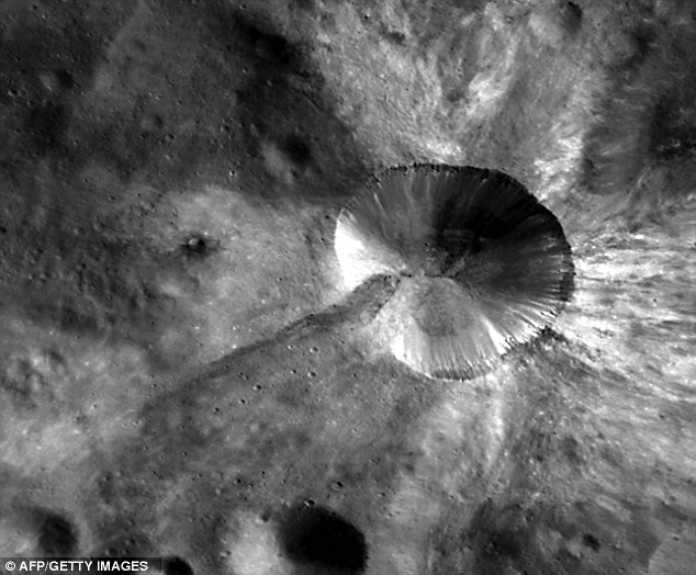 A crater on the asteroid Vesta shows the heavy bombardment the asteroid has suffered - expelling material out into space and towards the Earth