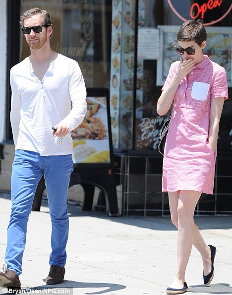 Pensive: Anne Hathaway walks with fiance Adam Shulman in Los Angeles following the cancellation of the Paris premiere of her new film The Dark Knight Rises