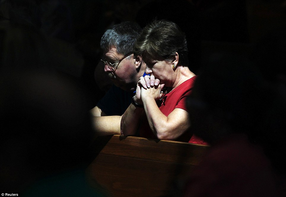 Reflection: People pray during a morning mass remembering the victims of the movie theatre shootings