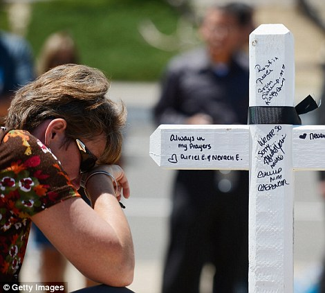 Prayer: Angie Terry, from Alabama, prays next to a white wood cross erected for victims who were  killed during last weekend's mass shooting at Century 16 movie theater