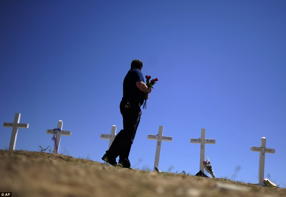 Memorial: Travis Hirko stands in front of the cross for Alex Sullivan at a memorial at in Aurora